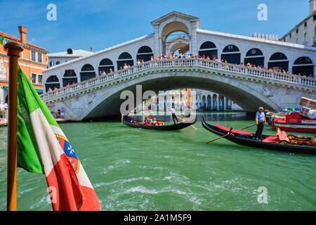 Italian maritime flag with Rialto bridge with gondolas in the bacground. Grand Canal, Venice, Italy - Stock Photo