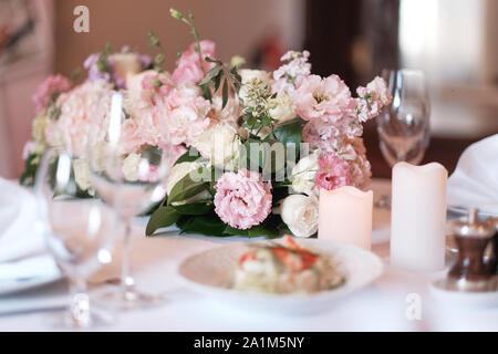 Bouquet on the table. Wine glasses in the foreground. Wedding Banquet or gala dinner. The chairs and table for guests, served with cutlery and crocker - Stock Photo