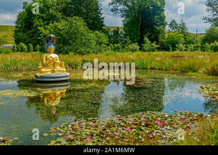 Statue of the Buddhist god Nagarjuna in a pond at the Kagyu Samye Ling Monastery and Tibetan Centre in Eskdalemuir, Dumfries and Galloway, Scotland. - Stock Photo