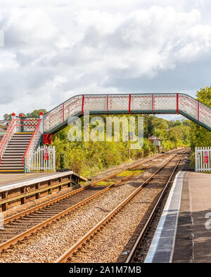 A colourful railway station footbridge at Llanfairpwllgwyngyll, Anglesea in Wales.   Railway lines run underneath and a blue sky with clouds overhead. - Stock Photo