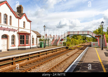 Station building and footbridge at  Llanfairpwllgwyngyll, in Wales known to have the longest place name in the UK. A blue sky is overhead. - Stock Photo