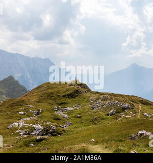 Person alone around Alps between huge Mountain Chains inside beautiful Nature. Summer Day Panorama in Julian Alps, Triglav National Park, Slovenia. - Stock Photo