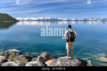 Man standing on a boulder and contemplating the Lake Tahoe, in Nevada, USA. - Stock Photo