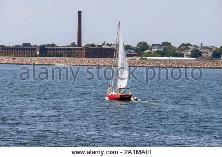 New Bedford, Massachusetts, USA – July 26, 2019: Sailboat working her way along  New Bedford shoreline - Stock Photo