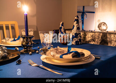 Christmas table decoration with wrapped gifts in background at candle light