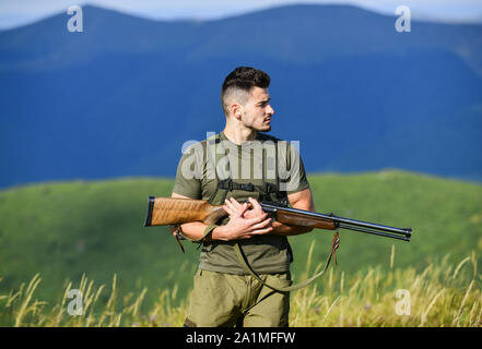 Security. military style. male in camouflage. army forces. sniper reach target mountain. man ready to fire. hunter hobby. muscular man hold weapon. purpose and success. soldier in the field. polygon. - Stock Photo