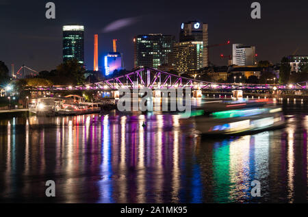 27 September 2019, Hessen, Frankfurt/Main: Illuminated in colour, the Iron Footbridge is reflected in the Main in front of the city's skyscrapers and the power station at the Westhafen, on the right an excursion ship (photo with long-time exposure). The pedestrian bridge was opened 150 years ago and the steel structure has become one of the city's landmarks. Photo: Frank Rumpenhorst/dpa - Stock Photo
