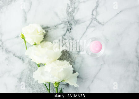 Pink transparent spray bottle and flowers on marble. Flat lay. Natural products for cleaning or body care concept - Stock Photo