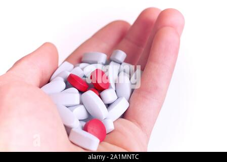 Drug abuse, self medication, placebo concept. Handful of red and blue pills on white background. - Stock Photo