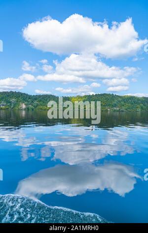 Reflected lake edge and white clouds on idyllic Lake Rotoiti near Rotorua New Zealand.