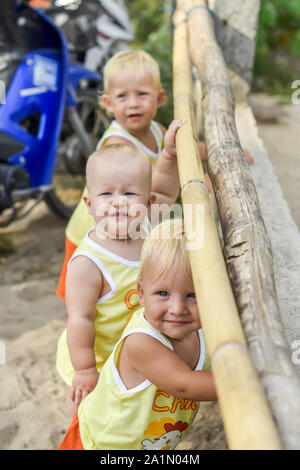 Three baby Toddler looking through fence on the hens and roosters in the henhouse. The yellow shirts. Two boys and one girl - Stock Photo