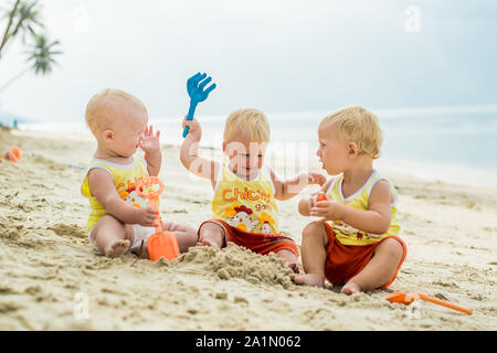 Three baby Toddler sitting on a tropical beach in Thailand and playing with sand toys. The yellow shirts. Two boys and one girl - Stock Photo