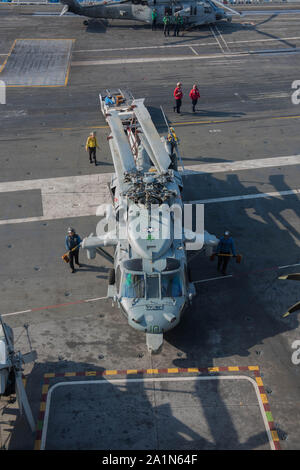 190926-N-XO654-0229  ATLANTIC OCEAN (Sept. 26, 2019) Sailors guide an MH-60S Sea Hawk, assigned to the 'Dusty Dogs' of Helicopter Sea Combat Squadron (HSC) 7, into place on the flight deck aboard the aircraft carrier USS Dwight D. Eisenhower (CVN 69). Ike, with embarked Carrier Air Wing 3, is underway conducting the Tailored Ship's Training Availability (TSTA) and Final Evaluation Problem (FEP) as part of the basic phase of the Optimized Fleet Response Plan. (U.S. Navy photo by Mass Communication Specialist 3rd Class Tatyana Freeman) - Stock Photo