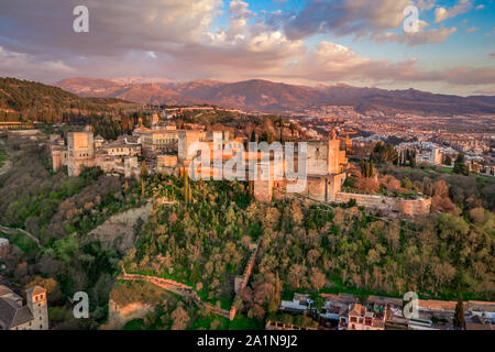Aerial sunset panorama view of the Alhambra fortress and palace complex with surrounding medieval walls and towers in Granada Andalusia Spain