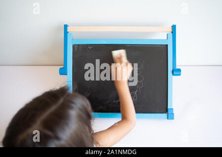 Small girl with long brown hair erasing small blackboard with white surroundings seen from behind - Stock Photo