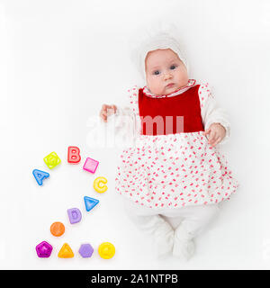 Portrait of a sweet infant baby girl wearing a red dress and bonnet, isolated on white in studio with number two from toys, cubes, letters and molds - Stock Photo