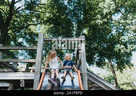 Two young children at the top of a slide on a play structure surrounded by trees