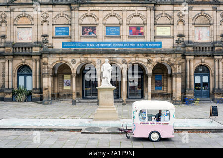 Quaint looking Pink and white mobile ice cream van with salesman, outside the York Art Gallery. - Stock Photo