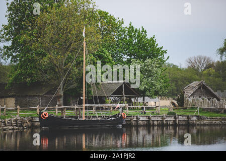 Old wooden viking huts in a village with ship moored at the bank. - Stock Photo