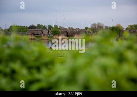 Old wooden viking huts in a village with modern windturbines in the background. Past vs Present. The world is racing forward. - Stock Photo