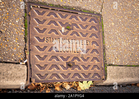 Manhole access cover in Southend on Sea, Essex, UK. Stanton & Staveley Ductile. Curb drain cover with autumn leaves. Space for copy - Stock Photo