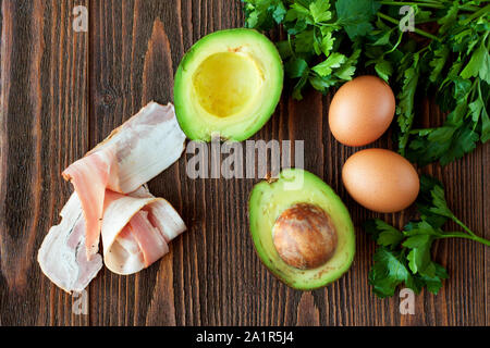 Avocado, eggs, bacon, parsley - ingredients for baked eggs in avocado - Stock Photo
