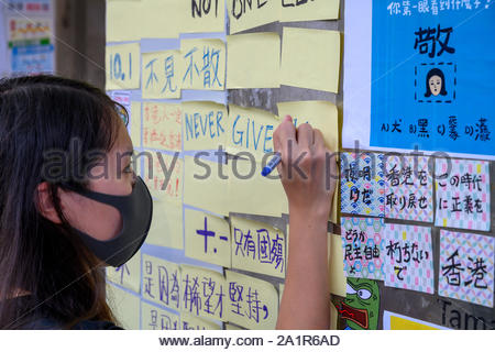 Tamar, Admiratly, Hong Kong, September 29 2019.  The fifth anniversary of the umbrella revolution. Tens of thousands gathered at Tamar for a rally to mark the beginning of the Occupy movement five years ago. A student writes a message on the Lennon Wall at Tamar during the anniversary event. - Stock Photo