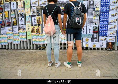 Tamar, Admiratly, Hong Kong, September 29 2019.  The fifth anniversary of the umbrella revolution. Tens of thousands gathered at Tamar for a rally to mark the beginning of the Occupy movement five years ago. A young couple holds hands while looking at the anniversary posters at the venue. - Stock Photo
