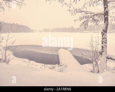 Unfrozen winter lake with snow-covered trees. Part frozen pond and walk around it in the winter on a snowy day - Stock Photo