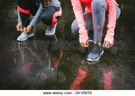 Close up of two female athletes lacing shoes and getting ready for urban running workout under the rain. Winter training and fitness lifestyle concept - Stock Photo