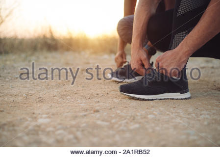 Outdoor running concept. Couple lacing sport shoes for preparing for training at sunset. - Stock Photo