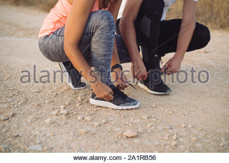 Outdoor running concept. Couple lacing sport shoes before training. - Stock Photo