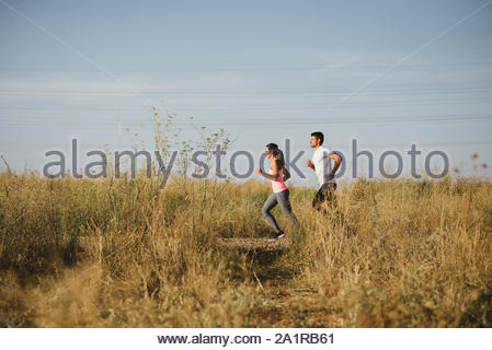 Two athletes running at sunset. Man and woman training together outdoor. - Stock Photo