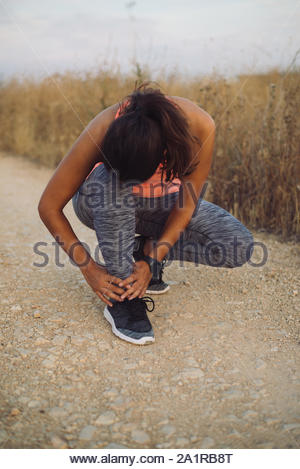 Female athlete suffering form running ankle injury during outdoor workout on dirt road. - Stock Photo