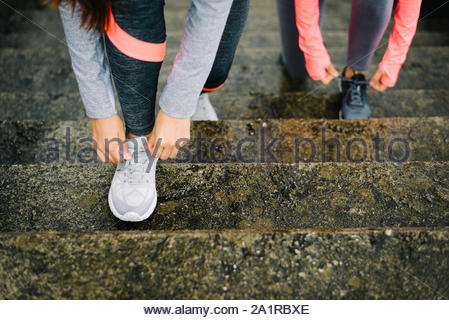 Urban running and fitness workout concept. Female athletes lacing sport shoes on wet stairs. - Stock Photo