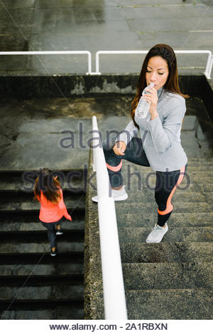 Urban fitness women running and working out outdoor under the rain. Two female friends doing hiit training climbing stairs. Latin beautiful sporty mod - Stock Photo