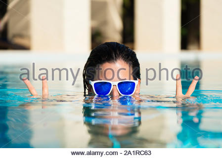 Summer fun and vacation concept. Playful woman doing success and victory gesture in swimming pool. - Stock Photo