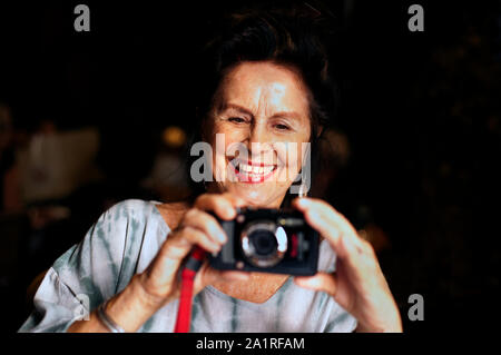 Attractive older woman smiling and taking a photograph. - Stock Photo