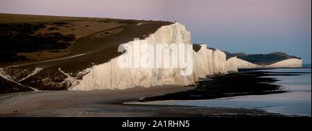A dramatic panoramic view of the Seven Sisters at sunset. The Seven Sisters are a series of white chalk cliffs by the English Channel. - Stock Photo