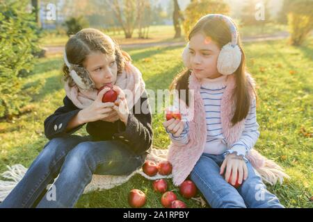 Children two girls eating red apples sitting in yellow autumn park, golden hour - Stock Photo