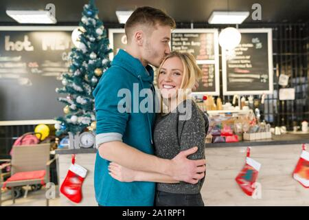 Kissing young couple near Christmas tree in cafe. - Stock Photo
