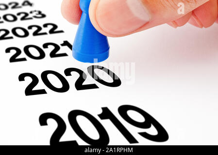 Hand moving a blue pawn from year 2019 to year 2020 printed on white paper. New year new beginning concept.