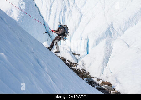 A man holding an ice axe rappels down an ice slope on the Matanuska Glacier in Alaska. - Stock Photo