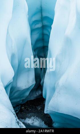Narrow canyon-like entrance looking into a large ice cave on the Matanuska Glacier in Alaska.