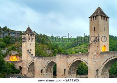 Medieval Pont Valentré bridge over the Lot River at dawn on cloudy morning, Cahors, Lot Department, Midi-Pyrénées, France - Stock Photo