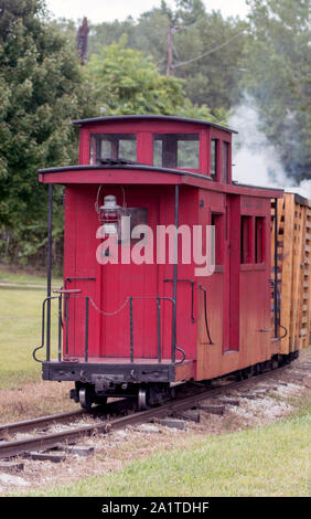 A little red caboose car is the last car on this miniature steam train ride - Stock Photo