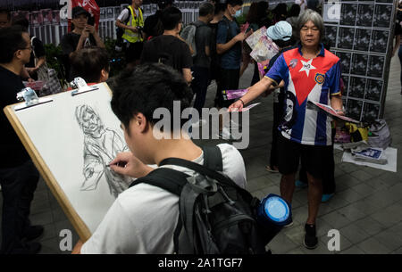 Hong Kong, China. 28th Sep, 2019. An artist sketches a protester handing out placards during the demonstration.Demonstrators gathered for an anti-authoritarian rally that marked the 5th anniversary of the beginning of the 2014 'Umbrella Movement'. Thousands of protesters gathered peacefully, but minor clashes between protesters and police escalated through the night, leading to a police dispersal operation. Protesters continue to clash with police as they reiterate their 5 demands. Credit: SOPA Images Limited/Alamy Live News - Stock Photo