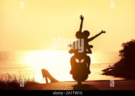 Unrecognizable couple with raised arms rides on scooter against sunset sea - Stock Photo