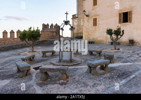 Cloister with benches and well in the Sanctuary of Sant Salvador Arta, Mallorca - Stock Photo