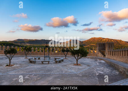 Cloister with benches and well in the Sanctuary of Sant Salvador Arta, Mallorca on the background mountains and clouds at sunset - Stock Photo